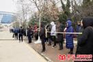 考生家长在警戒线外目送考生进考场。